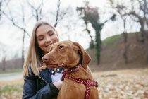 Hund mit Besitzer sitzen in herbstlichen park — Stockfoto