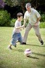 Маленький мальчик играет в футбол с его дед — стоковое фото