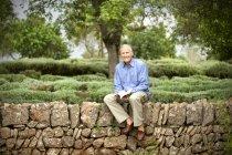 España, Mallorca, retrato de un anciano relajado sentado con un libro en una pared en el jardín - foto de stock