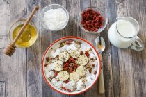 Bowl of muesli with banana slices, chia seeds, coconut chips and goji berries on dark wood — Stock Photo