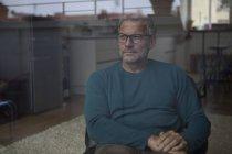 Uomo maturo che si siede dietro vetro guardando fuori — Foto stock