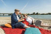 Senior couple relaxing with guitar on blanket on the beach — Stock Photo