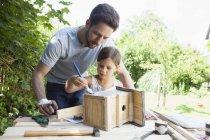 Kaukasischer Vater und seine Tochter malen ein Vogelhaus — Stockfoto