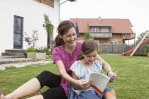 Smiling mother and daughter in garden reading book — Stock Photo