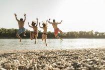 Amigos felizes pulando no rio na praia — Fotografia de Stock