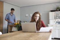 Donna a casa usando il portatile con uomo in verdure di taglio di sfondo — Foto stock