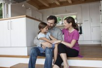 Happy family sitting on kitchen steps — Stock Photo