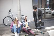 Homme d'affaires donnant un briquet à deux amies sur la rue de la ville — Photo de stock