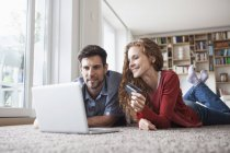 Happy couple lying on floor shopping online — Stock Photo
