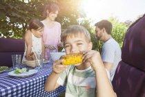 Boy eating a corn cob on a family barbecue in garden — Stock Photo