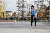 Junge Frau mit Skateboard Blick auf Handy — Stockfoto