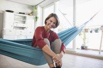 Mulher feliz em casa sentado na cama de rede — Fotografia de Stock
