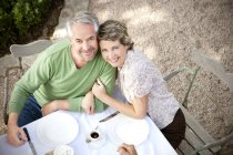 Portrait of smiling couple sitting at laid table in the garden looking up to camera — Stock Photo