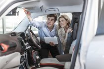 Car dealer showing new car to woman — Stock Photo