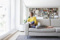 Relaxed woman at home sitting on couch — Stock Photo