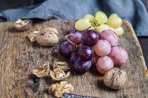 Vista del primo piano del bordo di legno con le noci e l'uva — Foto stock