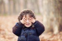 Bambino in giacca con cappuccio occhi di chiusura con le mani — Foto stock