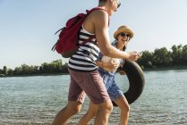 Casal jovem com tubo interno e telefone celular andando na beira do rio — Fotografia de Stock