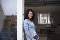 Portrait de femme souriante, appuyé contre la porte du balcon — Photo de stock