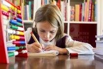 Retrato de chica haciendo tareas en la mesa - foto de stock
