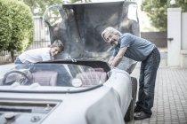 Abuelo y nieto restaurando un coche juntos y mirando a la cámara - foto de stock