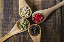 Elevated view of four wooden spoons of different peppercorns on wooden surface — Stock Photo