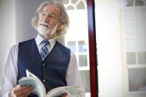 Старший професор тримає книгу поруч із вікном — стокове фото