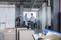 Due uomini d'affari in piedi e parlando nel nuovo ufficio — Foto stock
