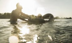 Happy couple with inner tube in water — Stock Photo