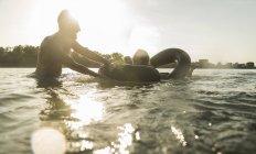 Couple heureux avec chambre à air dans l'eau — Photo de stock