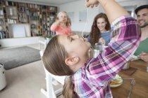 Bambina mangiando spaghetti mentre i suoi genitori e la sorella la guardano — Foto stock