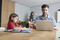 Uomo che si siede al tavolo di cucina utilizzando computer portatile mentre sua figlia piccola pittura — Foto stock