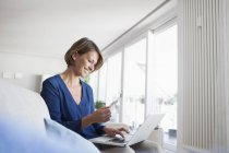 Smiling woman at home shopping online — Stock Photo