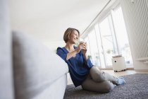 Relaxed woman at home leaning at couch — Stock Photo