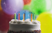 Blown out birthday candles on cake in front of balloons — Stock Photo