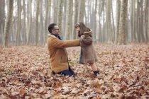 Pai brincando com sua filha no parque sentado em folhas outonais — Fotografia de Stock