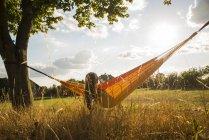 Резервного зору жінка з навушниками лежить в гамаку відпочинку на природі — стокове фото