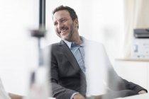 Homme d'affaires souriant assis dans le Bureau — Photo de stock
