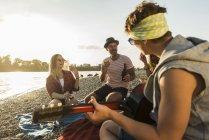 Amici con chitarra che si rilassano sul lungofiume al tramonto — Foto stock