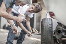 Großvater lehrt Enkel Auto Radwechsel — Stockfoto