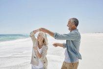 Coppia che balla sulla spiaggia di sabbia — Foto stock