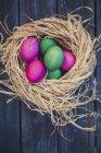Vista del primo piano delle uova di Pasqua verde e rosa in nido — Foto stock