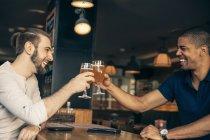 Deux hommes heureux dans un bar sonnante verres à bière — Photo de stock