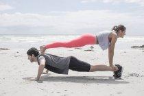 Joven hombre y mujer haciendo ejercicio en la playa - foto de stock