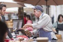 Мужчина продает сосиски на городской рынок — стоковое фото