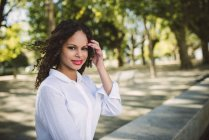 Lächelnde Frau, stehend im park — Stockfoto