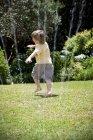 Маленький мальчик играет с газонным разбрызгивателем в саду — стоковое фото