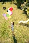 Счастливая женщина, стоя в саду Холдинг разноцветных шаров — стоковое фото
