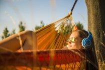 Жінка з сонцезахисні окуляри і навушники, розслаблюючі в гамаку — стокове фото