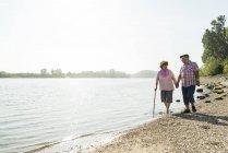 Coppia anziana che cammina mano nella mano sul lungofiume — Foto stock